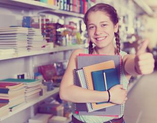 Happy schoolgirl with copybooks in shop
