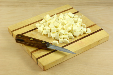 Chopped fresh mozzarella cheese with kitchen knife on wooden cutting board