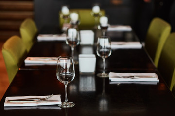 Dining table served with glasses, forks and knifes
