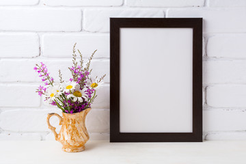 Black brown  frame mockup with chamomile and purple flowers in golden pitcher