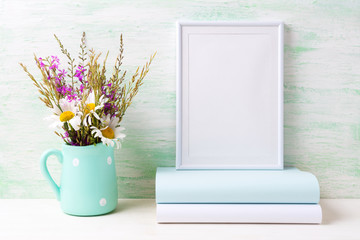White frame mockup with chamomile and purple flowers in mint green pitcher and books