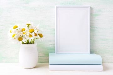 White frame mockup with chamomile bouquet in rustic vase and books
