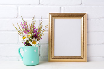 Golden  frame mockup with chamomile and purple flowers in mint green pitcher
