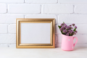 Golden  landscape frame mockup with purple flowers in pink rustic pitcher