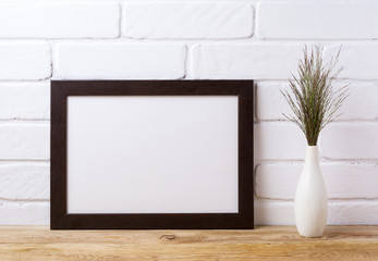 Black brown  landscape frame mockup with dark grass in elegant vase