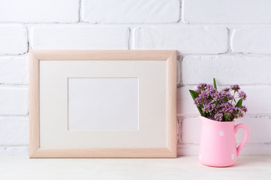 Wooden landscape frame mockup with purple flowers in pink rustic pitcher