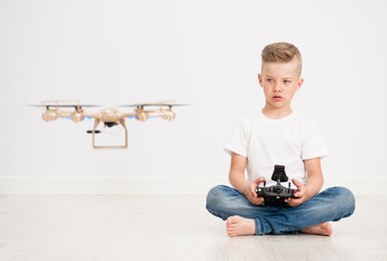 Boy is operating the drone by remote control