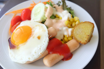 Salad vegetables, sausage, fried eggs in a white plate on the table