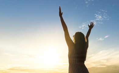 Brave happy young woman raising hands up in the air and open arms to sky. Enjoying life. Sunny healthy lifestyle concept in sunset.