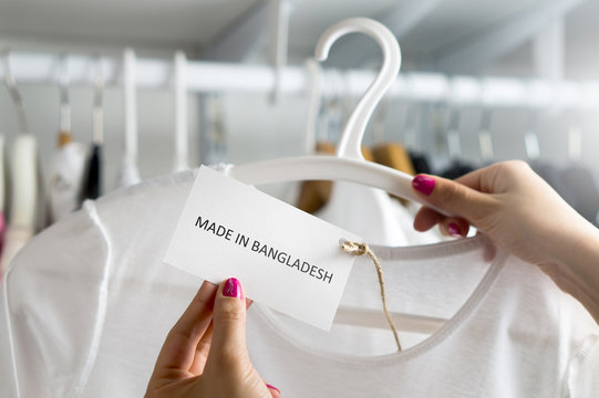 T-shirt made in Bangladesh. Customer looking at the origin and import country of a cheap fashion product in clothes store or shop. Ethical consumer behavior. Woman holding label and price tag with tex