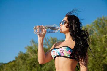 Beautiful fit woman in swimsiut drink fresh water