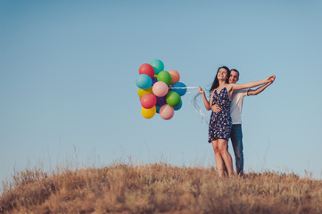 Couple in love for a walk in nature with baloons