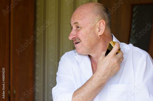 Portrait of a mature stylish man in white shirt , tasting perfume ...