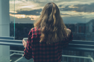Woman drinking coffee on balcony at sunrise