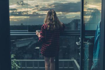 Woman drinking coffee on balcony at sunrise