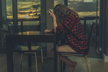Tired woman drinking coffee by window at sunrise