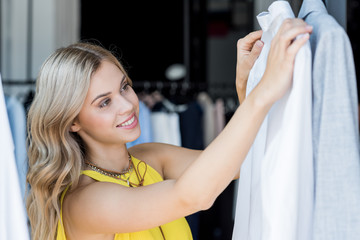 smiling blonde woman choosing shirt in store