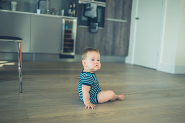 Little baby sitting on the floor in kitchen