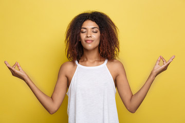Portrait of beautiful calm young african american black female with Afro hairstyle practicing yoga indoors, meditating, holding hands in mudra gesture.