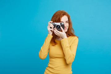 Travel and People Concept - Headshot Portrait of happy ginger red hair girl with playing with vintage camera in happy expression. Pastel blue background. Copy Space.