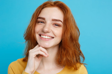 Close up Portrait young beautiful attractive redhair girl smiling looking at camera. Blue Pastel Background.