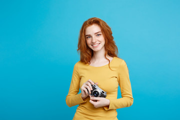 Close up Portrait young beautiful attractive ginger girl happy smiling with vintage camera and ready to travel. Isolated on Blue Pastel Background. Copy space.