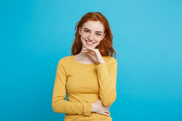 Lifestyle concept - Portrait of young stylish freckled girl laughing with hand on chin looking at camera. Blue Pastel Background. Copy space.