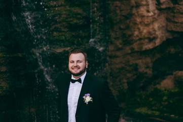 Groom in a suit and a bow tie for a walk