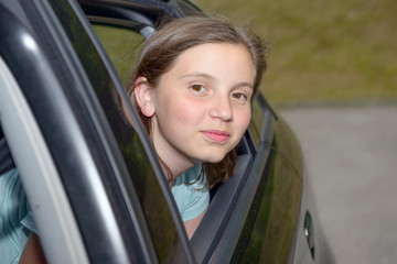 young teenage girl sitting in a car
