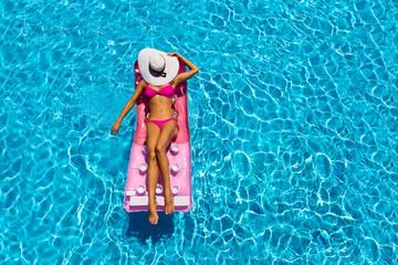 Attraktive Frau im Bikini treibt auf einer Luftmatratze im Pool und sonnt sich