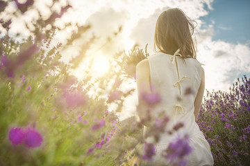 Back of young slim girl through lavender flowers. Evening on the lavender field. Enjoy the summer! unrecognizable portrait
