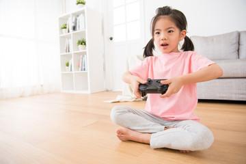 happy little daughter focus on using game joystick