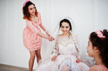 Bridesmaids helping bride to put her wedding shoes on and get ready for her wedding.