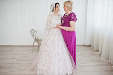 Lovely bride in wedding gown posing with her mother in purple long dress.