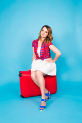 Pretty woman is sitting on red suitcase. Beauty, fashion, travel and people concept