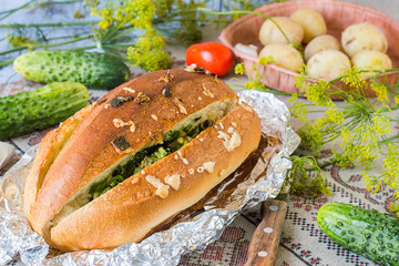 Bread for a picnic. Homemade bread with cheese, garlic, green onion and herbs in foil on a linen tablecloth. Next to the fresh vegetables and boiled potatoes.