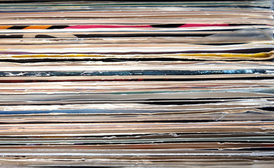 Horizontal pile of many close standing vinyl records covers as background front view close up