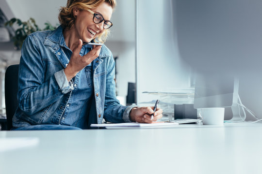 Smiling young businesswoman working at her desk