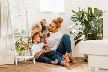 mother and daughter playing with teddy bear