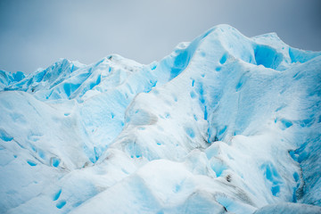 The blue glacier rises and shines in the daylight. Shevelev.