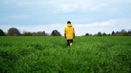 man in yellow raincoat in field
