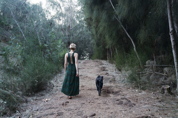 woman with dog walking a forest path