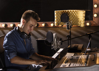 Musician working and producing music in his modern sound studio