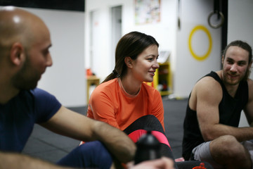 Three friends sitting on floor and having conversation after exercise. People workout in gym.
