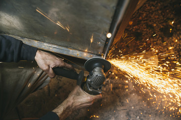Closeup of caucasian hands grinding metal with angle grinder