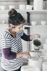 Portrait of female ceramic artist pouring slip into mould