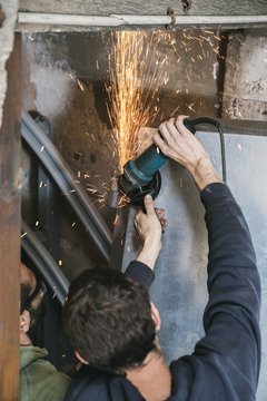 Two metal workers using a disc angle grinder on metal hinges