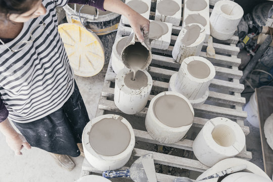 Woman artist poring ceramic slip into a casting mould