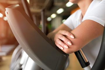 Closeup of female exercising on elliptical machine