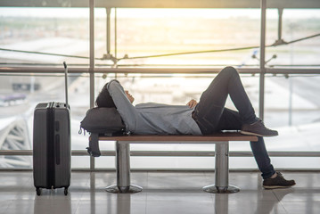 Young Asian man with his suitcase luggage and backpack lying on bench while waiting for connecting flight in the international airport terminal, travel lifestyle